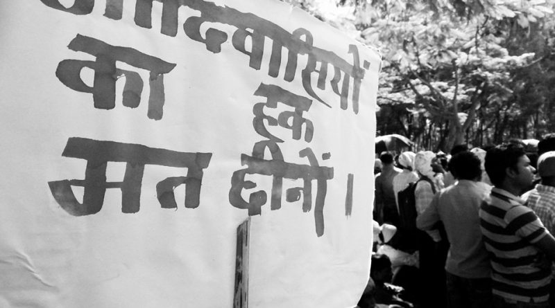 "Photo of a protest banner that says in Hindi ""Do not steal the rights of Adivasis""."